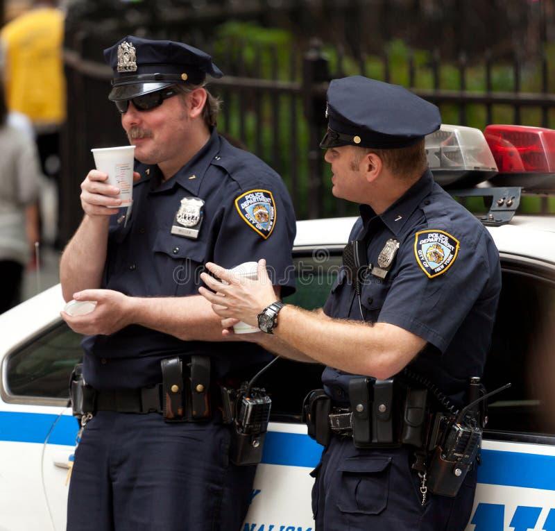 Twee politiemannen terwijl het drinken van een kop van koffie in NYC stock afbeeldingen