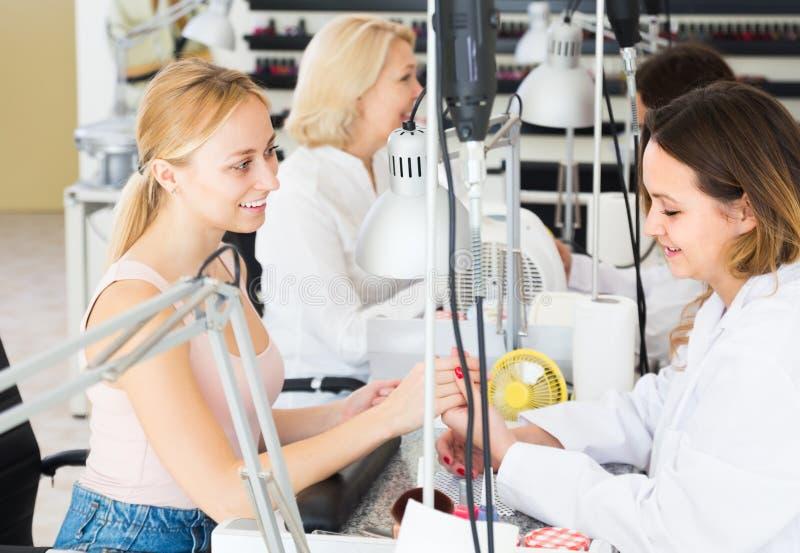 Twee positieve vrouwen die manicure doen stock fotografie