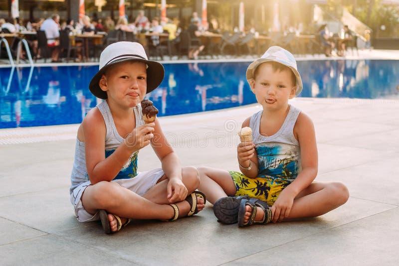Twee pre-school jongens in hoeden zitten door de openluchtpool van het hotel en eten roomijs in een wafelkegel Jonge geitjes en r stock foto