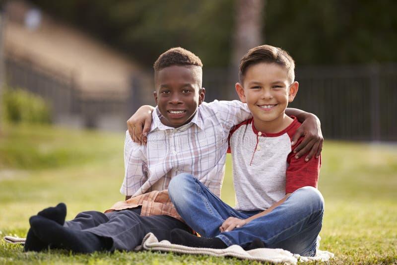 Twee pre-tiener mannelijke vrienden die op het gras in een park, wapens rond elkaar zitten, die aan camera kijken royalty-vrije stock afbeelding
