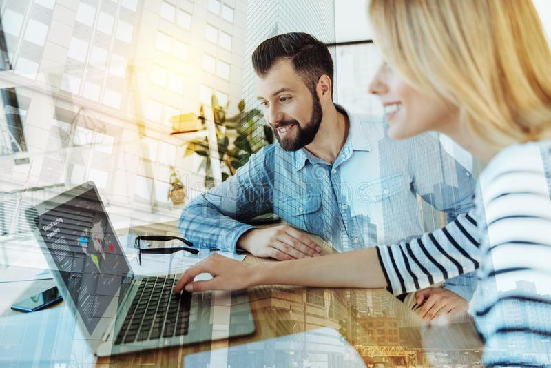 Twee prettige tevreden arbeiders die en laptop glimlachen met behulp van stock foto's