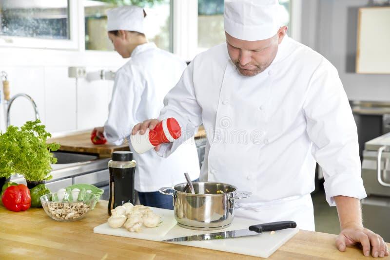 Twee professionele chef-koks die voedsel in grote keuken voorbereiden royalty-vrije stock fotografie