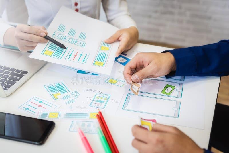 Twee programmeurs werkende schetsen voor mobiele telefoontoepassing in bureau Het concept van de gebruikerservaring stock afbeelding
