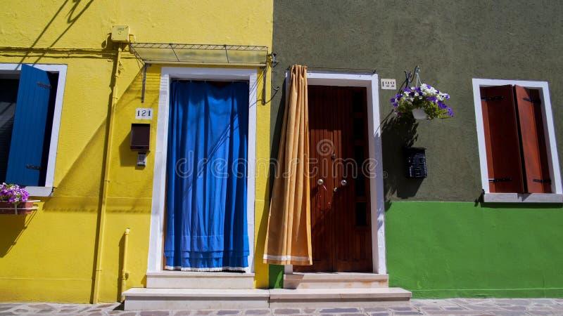 Twee propere naburige huizen met gesloten en open deuren, gastvrijheidstradities stock foto