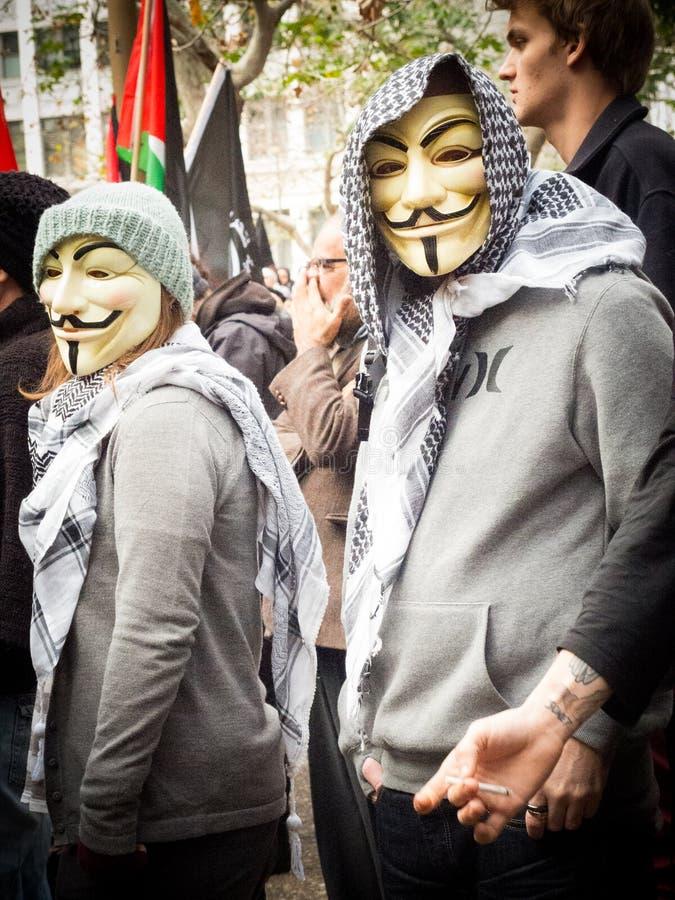 Twee protesteerders die het Anonieme masker dragen in Sydney townhall stock fotografie