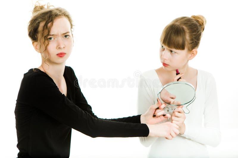 Twee puberteitmeisjes in zwart-witte kleding kibbelen om een spiegel ertoe te brengen om een merk omhoog te maken - zusterrivalit royalty-vrije stock foto