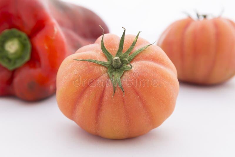 Twee R.A.F.-tomaten met Spaanse peper op witte achtergrond stock foto