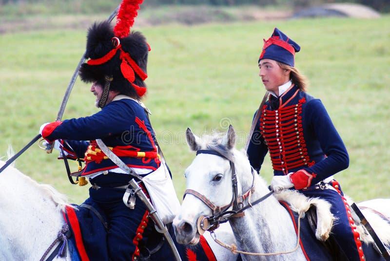 Twee reenactors kleedden zich aangezien Napoleonic oorlogsmilitairen paarden berijden stock afbeelding
