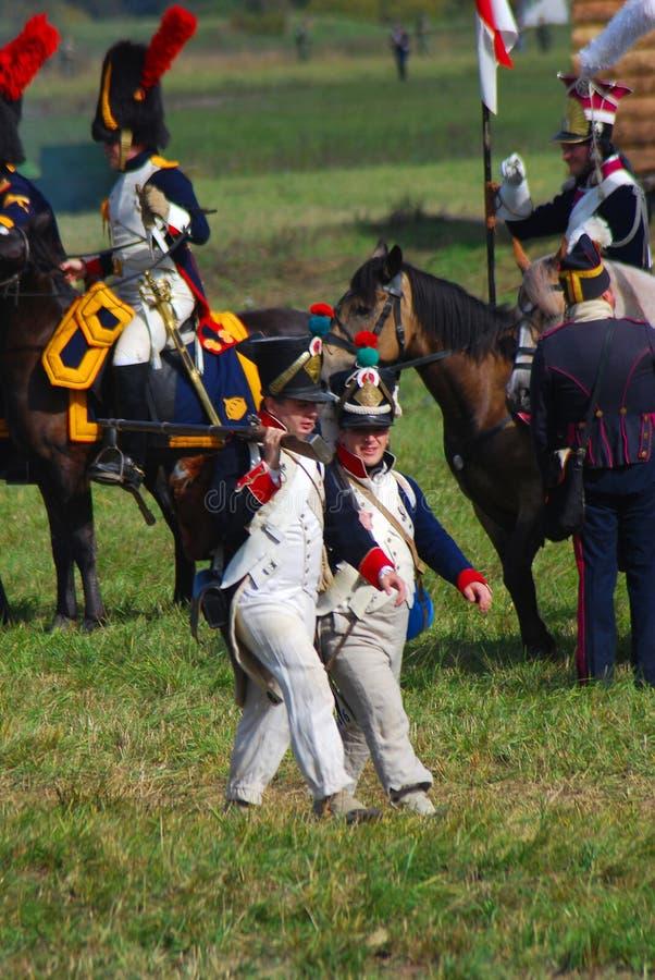 Twee reenactors kleedden zich aangezien Napoleonic oorlogsmilitairen paarden berijden stock foto's