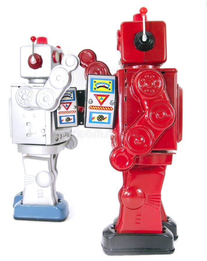 Twee retro robots hoge vijf geïsoleerd elkaar stock afbeelding
