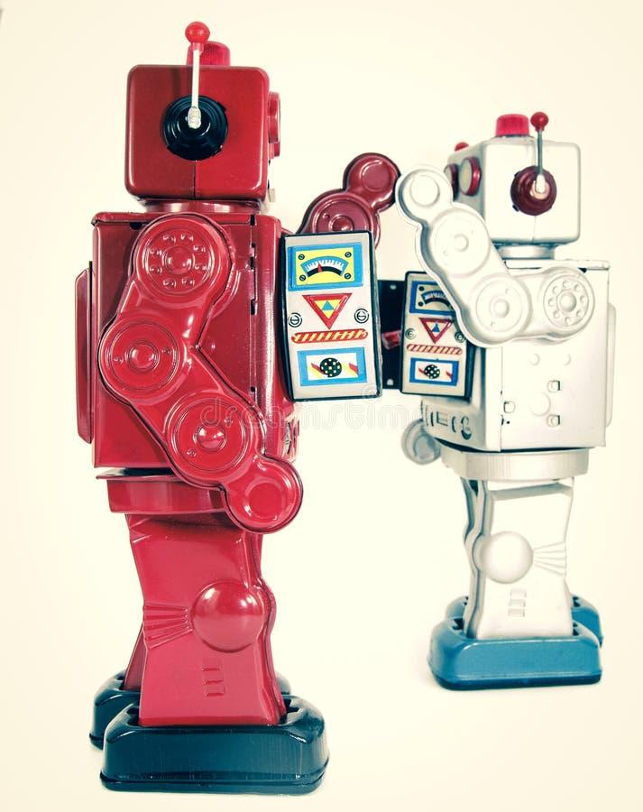 Twee retro robots hoge vijf geïsoleerd elkaar stock foto's