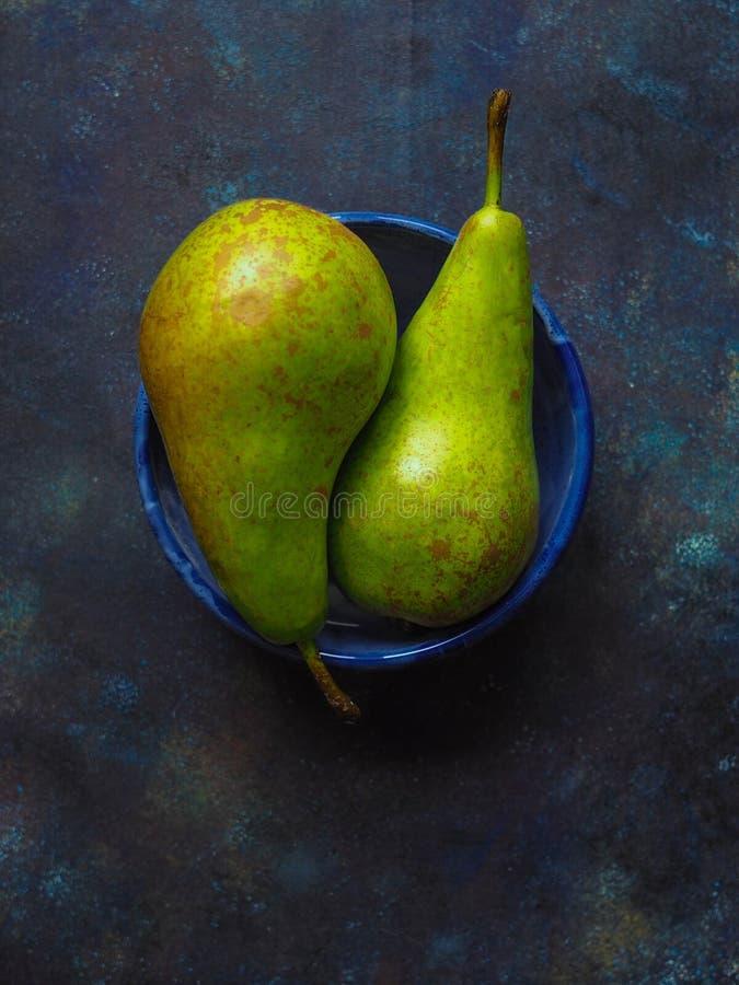 Twee rijpe geelgroene peren in een blauwe kom royalty-vrije stock fotografie
