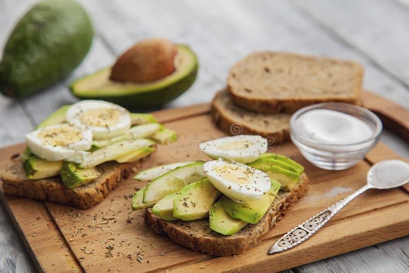 twee rijpe gesneden smakelijke avocadosandwiches met ei en kruiden op een houten Raad Concept Keto dieet royalty-vrije stock afbeeldingen