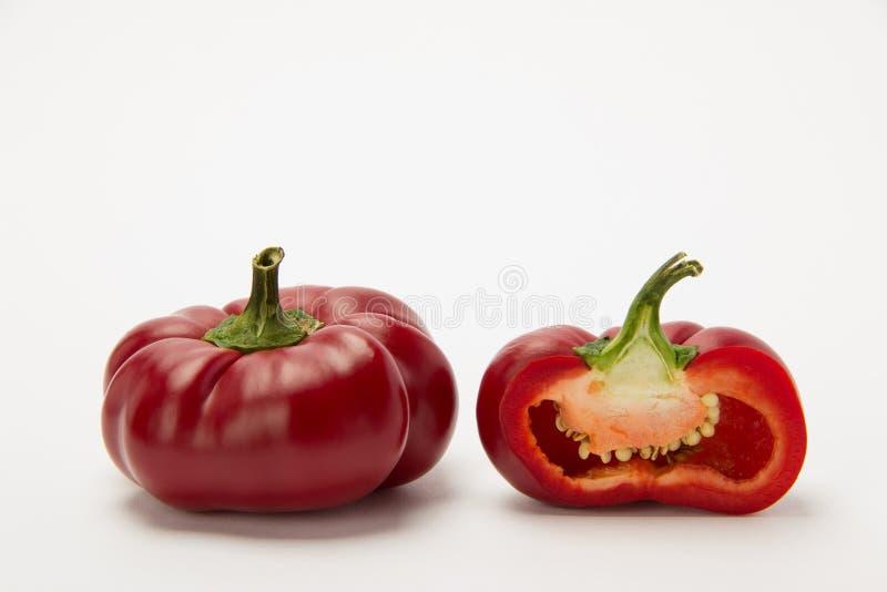 Twee rijpe Spaanse pepers in een besnoeiing op een witte achtergrond stock afbeelding