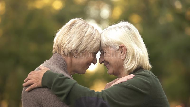 Twee rijpe vrouwelijke elkaar koesteren en vrienden die strak, gelukkige vergadering glimlachen royalty-vrije stock afbeeldingen