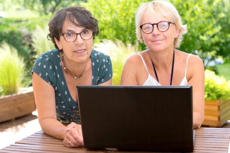 Twee rijpe vrouwenvrienden die laptop, op het tuinterras met behulp van royalty-vrije stock fotografie