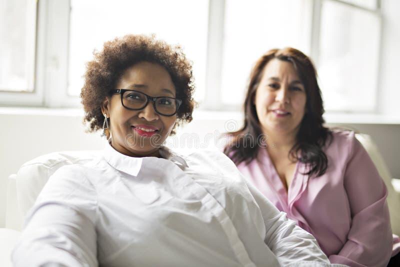 Twee rijpe vrouwenzitting op bank thuis stock foto