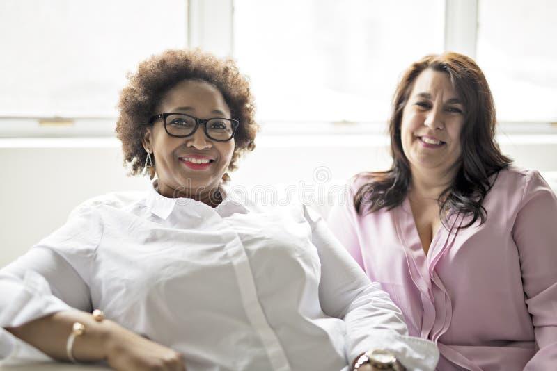 Twee rijpe vrouwenzitting op bank thuis stock fotografie