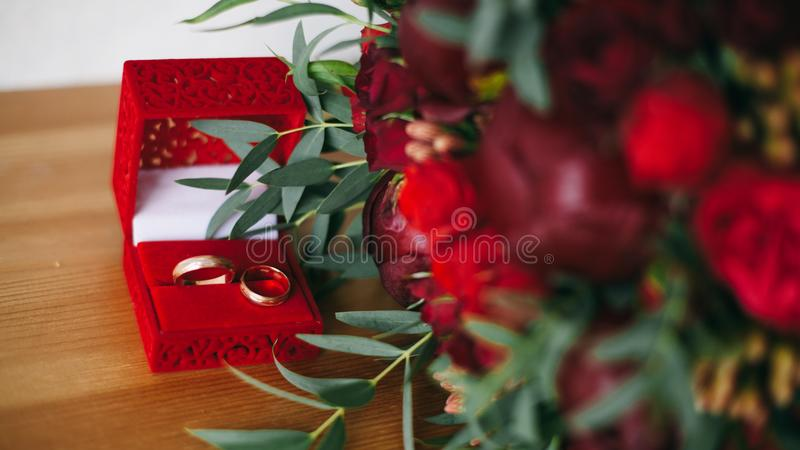 Twee ringen bij doos dichtbij bloemen stock fotografie