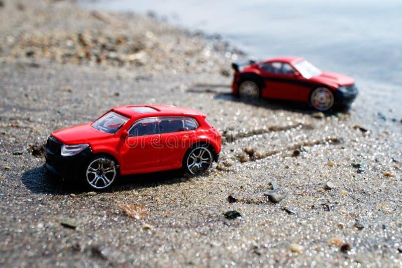 Twee rode auto's op het strand, van de rest op het zand buiten verlaten sporen op een de zomerdag royalty-vrije stock foto's
