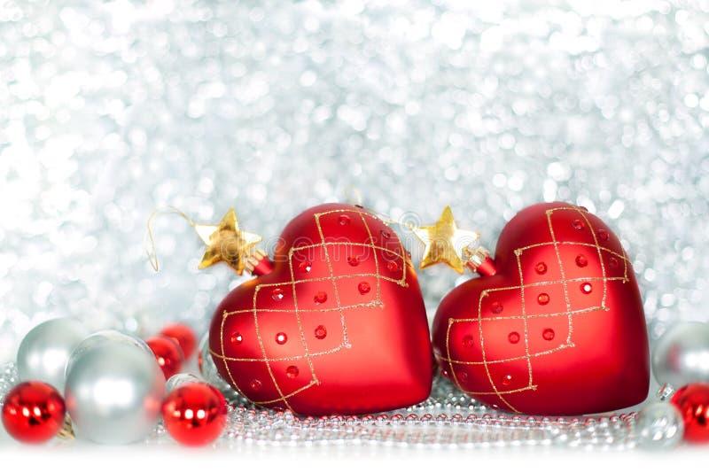 Twee rode ballen van het Kerstboomglas in de vorm van hart met gouden sterren en zilveren en rode ballen op glanzend fonkelend kl royalty-vrije stock foto's