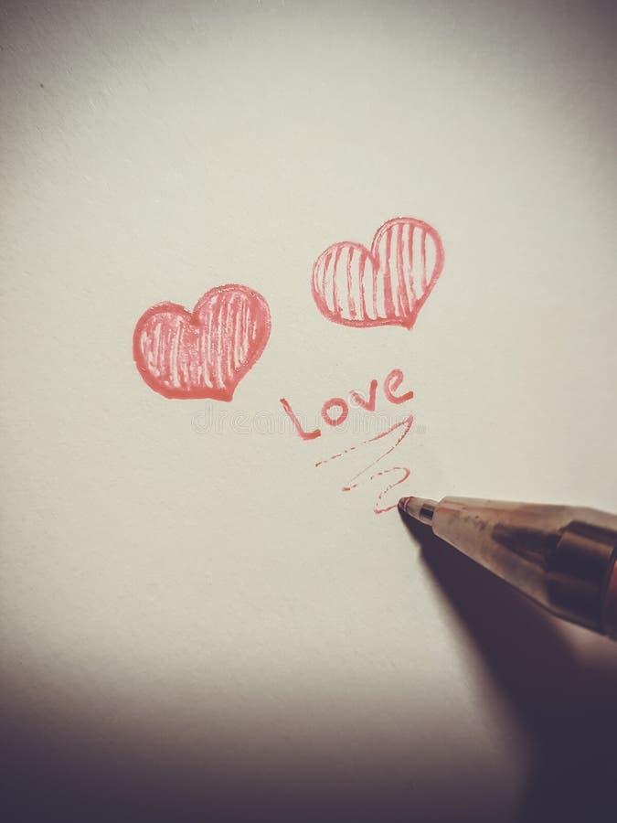 Twee rode harten en een pen op een lichte achtergrond De groetkaart van de procestekening voor Valentijnskaartendag royalty-vrije stock afbeelding