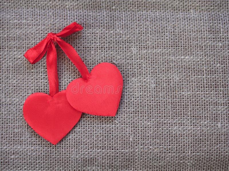 Twee rode harten liggen samen op een linnenachtergrond stock foto's