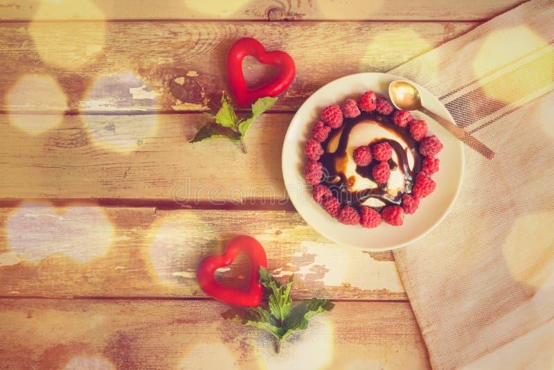 Twee rode harten met muntbladeren en eigengemaakte Italiaanse cotta van dessertpanna met verse framboos en chocoladestroop royalty-vrije stock foto's