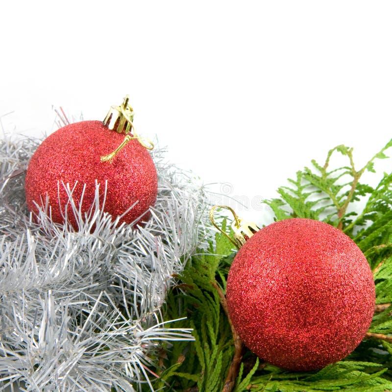 Twee rode Kerstmisballen met takken en lint stock afbeelding