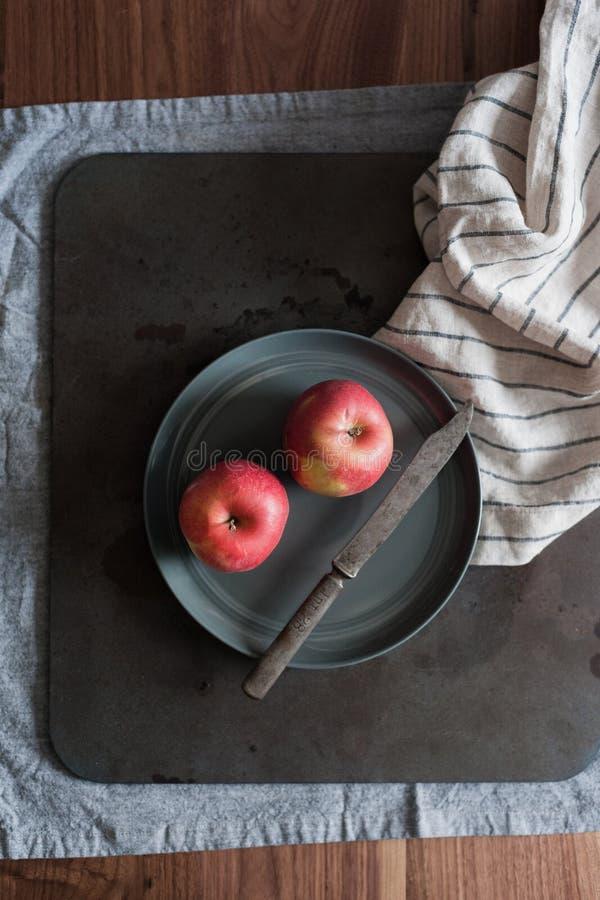 Twee rode organische appelen liggen op een grijze plaat met een mes op een donkere achtergrond op een houten lijst naast het linn stock foto's