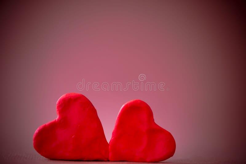 Twee rode plasticineharten tegen purpere achtergrond Het concept Valentine& x27; s Dag royalty-vrije stock afbeelding