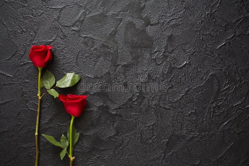 Twee rode rozen op een donkere, zwarte steenachtergrond Plaats voor tekst stock foto's