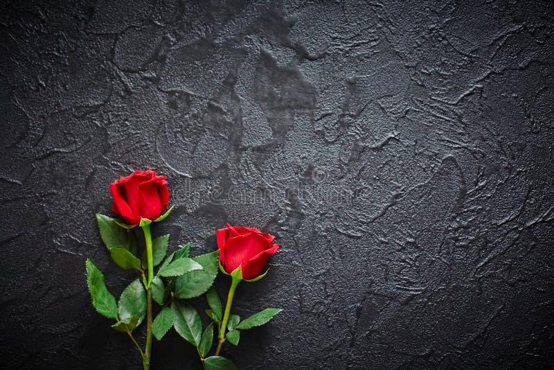 Twee rode rozen op een donkere, zwarte steenachtergrond Plaats voor tekst stock afbeeldingen