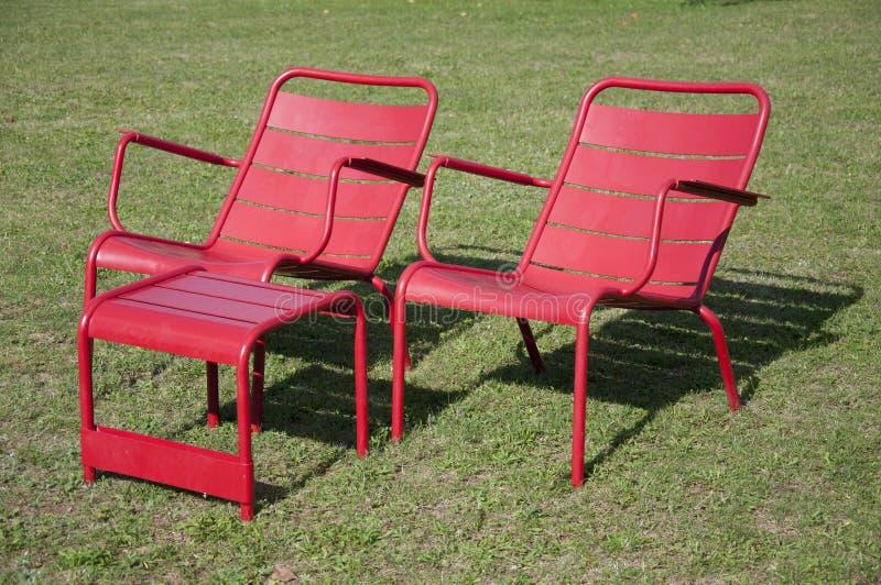 Twee rode stoelen en een rode lijst in de middagzon stock fotografie