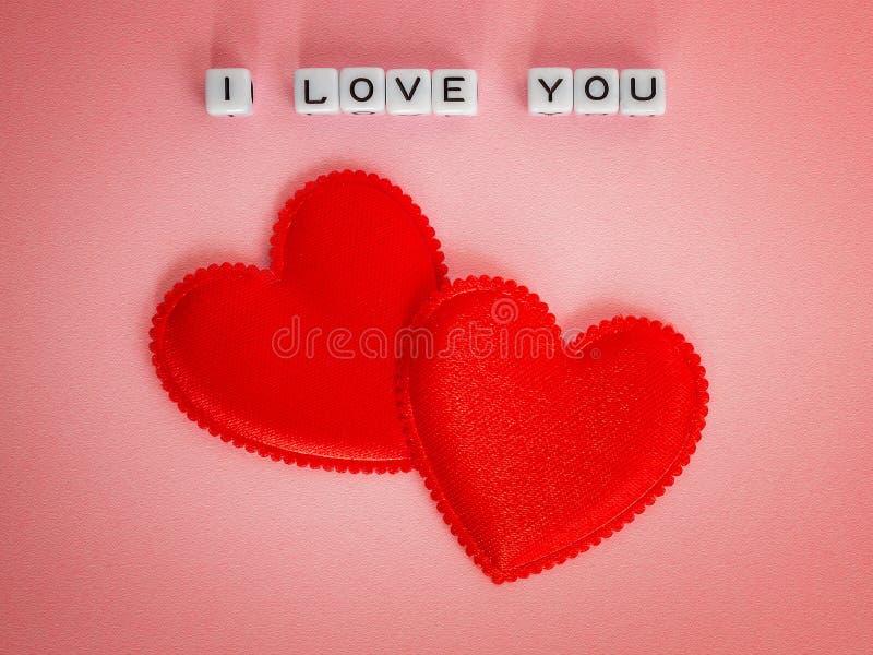 Twee rode valentijnskaartharten en inschrijving I houden van u maakten van witte alfphabetkubussen op pastelkleur roze achtergron stock foto's