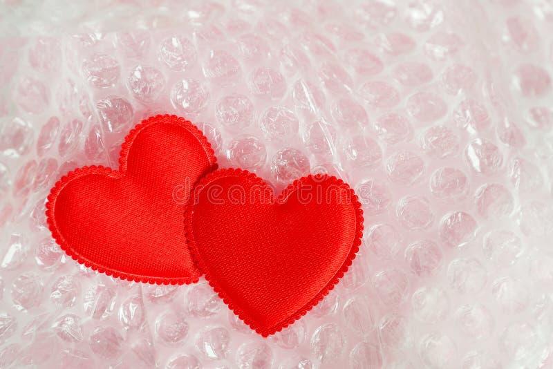 Twee rode valentijnskaartharten worden ingepakt in een transparante bellenomslag Het concept liefde, Valentine Day, de breekbaarh stock afbeelding