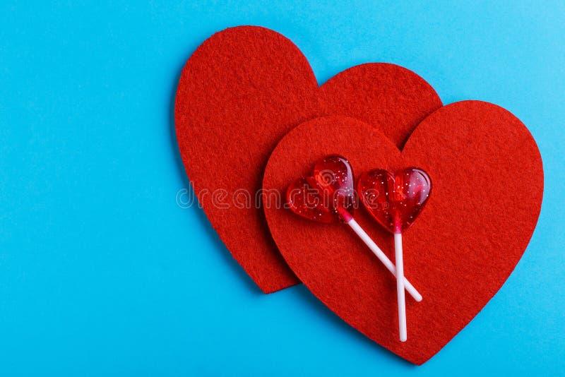 Twee rode zoete smakelijke lollys en twee voelden harten royalty-vrije stock afbeelding