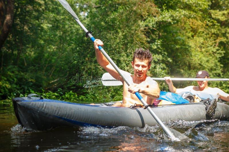 Twee roeiers in boot met roeispanen in handen op de rivier op de zomerdag De jonge sportenkerels zwemmen een kano langs de rivier royalty-vrije stock foto's