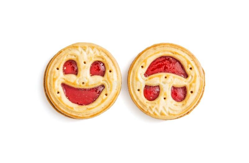 Twee ronde koekjes die gezichten, humoristisch zoet geïsoleerd voedsel glimlachen, stock fotografie