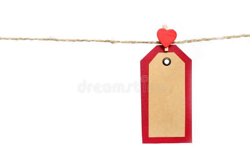 Twee rood en pakpapiermarkeringen die op de kabel door hartvorm hangen stock fotografie