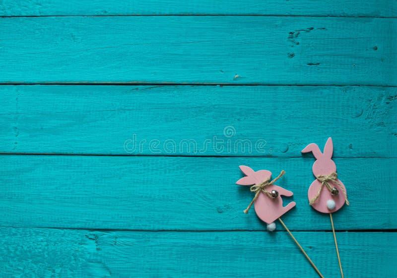 Twee roze Pasen bunnys op een blauwe houten achtergrond stock foto
