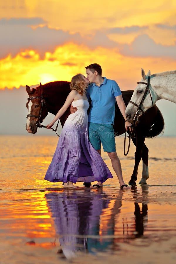 Twee ruiters op horseback bij zonsondergang op het strand De minnaars berijden hors stock foto's