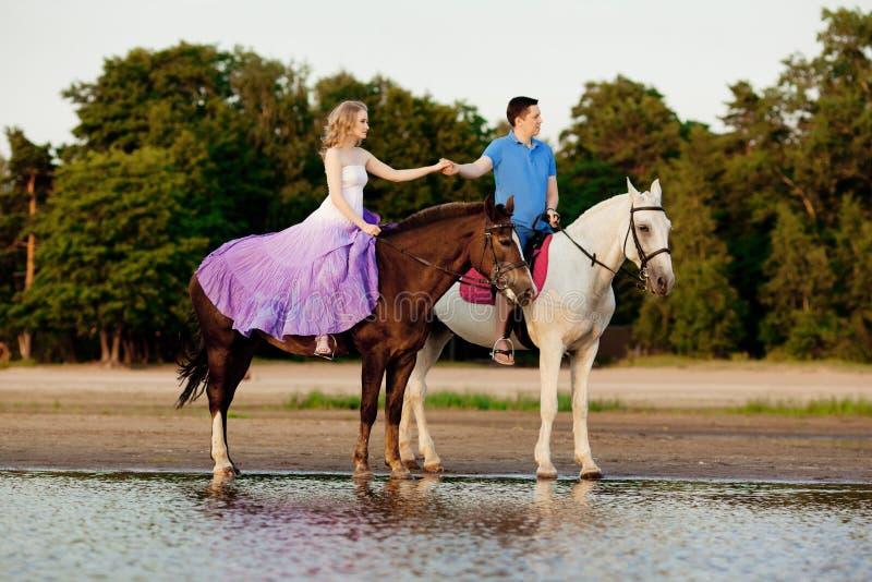 Twee ruiters op horseback bij zonsondergang op het strand De minnaars berijden hors royalty-vrije stock afbeelding