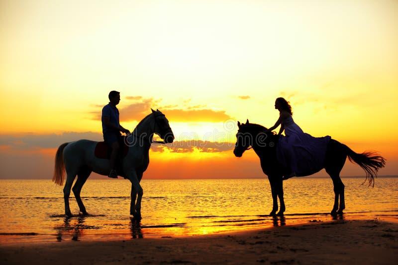 Twee ruiters op horseback bij zonsondergang op het strand De minnaars berijden hors royalty-vrije stock fotografie
