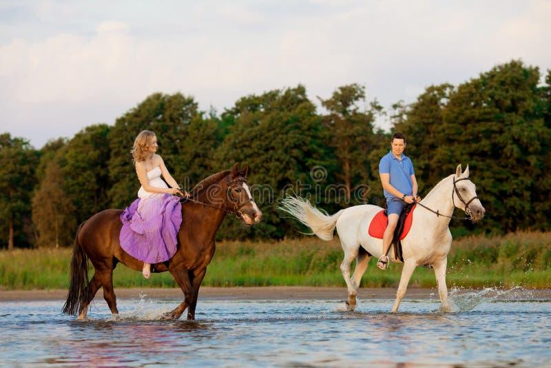 Twee ruiters op horseback bij zonsondergang op het strand De minnaars berijden hors stock afbeelding