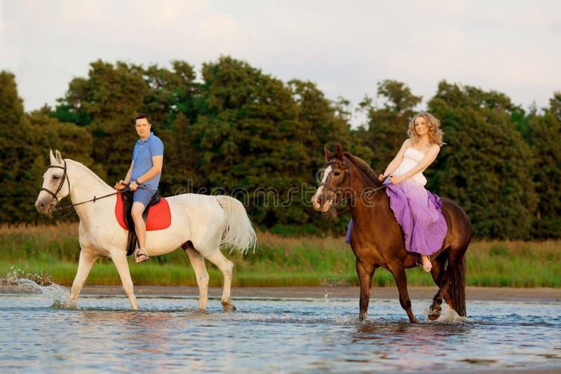 Twee ruiters op horseback bij zonsondergang op het strand De minnaars berijden hors stock fotografie