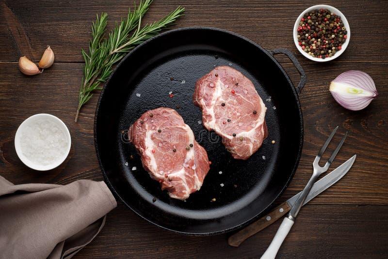 Twee ruw varkensvleeslapje vlees op pan op rustieke houten lijst royalty-vrije stock foto