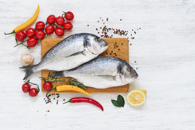 Twee ruwe doradavissen met groenten op houten scherpe raad Gezond voedselconcept Hoogste mening, exemplaarruimte Mediterrane zeev royalty-vrije stock foto