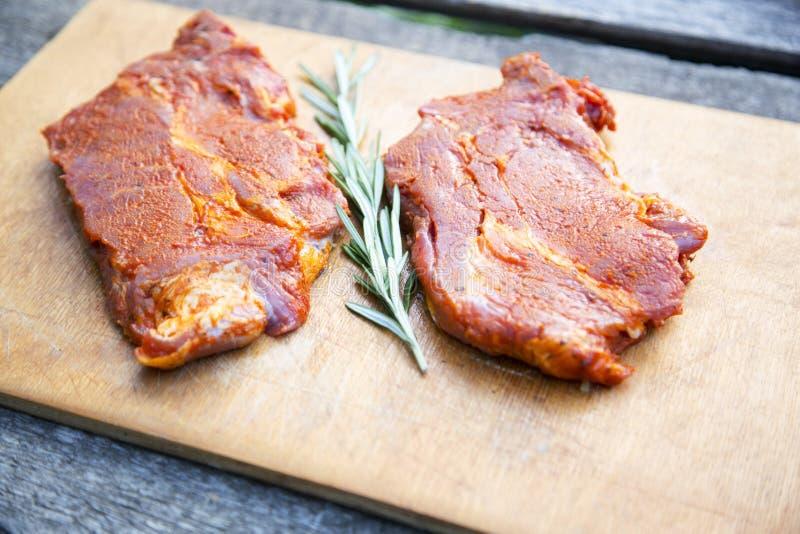 Twee ruwe lapjes vlees met kruiden op houten rustieke raad Klaar voor coo stock afbeelding