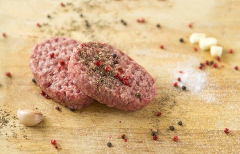 Twee ruwe rundvleeslapjes vlees met kruiden op een houten Raad, knoflook, zout royalty-vrije stock afbeelding